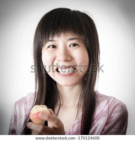 healthy beautiful young asian woman eating fruit peach - stock photo