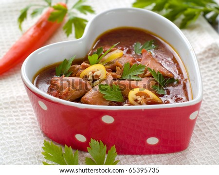 Healthy beef stew in heart shaped bowl  with parsley and chili