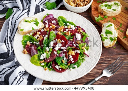Healthy Beet Salad with fresh sweet baby spinach, kale lettuce, nuts, feta cheese and toast with melted cheese. - stock photo