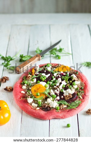 Healthy beetroot pizza with peas, feta, walnuts and rocket - stock photo