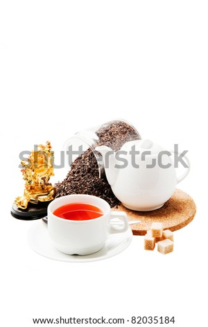 Healthy black tea in a white cup and a jar with dry  tea, and idol of prosperity statuette. Isolated. - stock photo