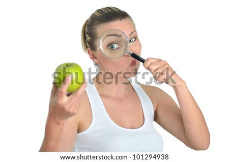 Healthy blondy happy woman eats and looks apples with magnifying glasses - stock photo