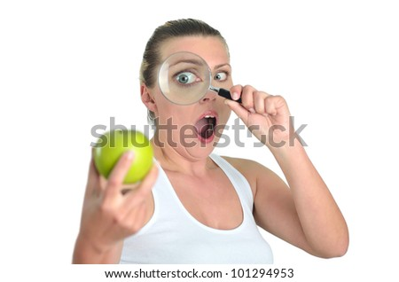 Healthy blondy happy woman eats and looks apples with magnifying glasses