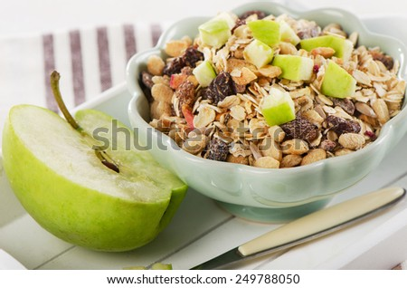 Healthy bowl of muesli and  green apple for a healthy breakfast - stock photo