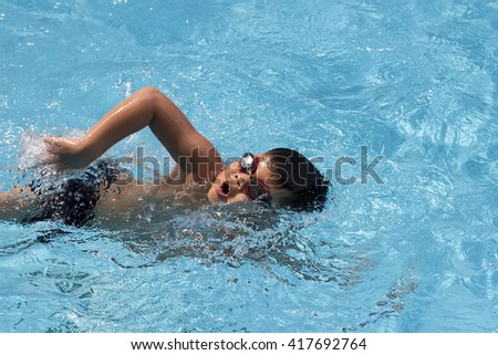healthy boy front stroke swims in swimming pool , Asian young kid training with swim goggles  - stock photo