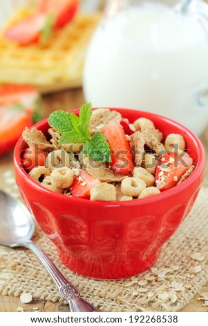 Healthy breakfast - a bowl of bran flakes mixed with oatmeal and fresh strawberries, decorated - stock photo