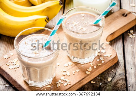Healthy breakfast: banana smoothie with oatmeal, peanut butter and milk - stock photo