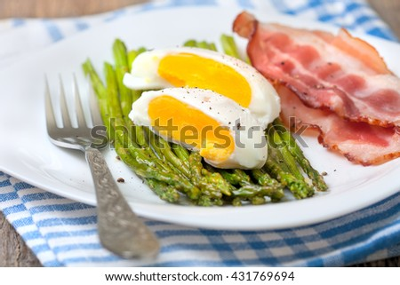 healthy breakfast:  boiled egg, baked asparagus on a wooden background close up - stock photo