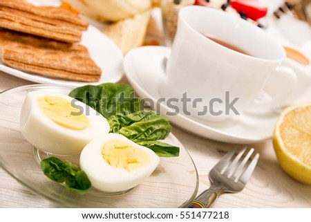 Healthy breakfast. Boiled eggs with spinach, cup of tea, cookies on white table.