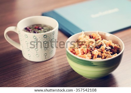 healthy breakfast bowl with herbal tea in the cup and book on the table