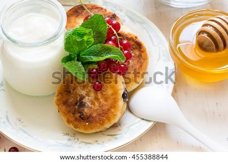 Healthy breakfast: cheesecakes, muesli, yogurt, honey, fresh berries and juice on white wooden background - stock photo