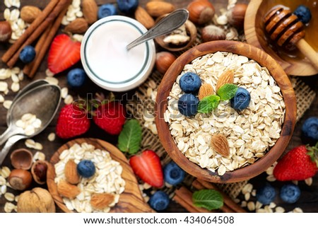 Healthy breakfast concept with oats, yogurt, fresh blueberries, strawberries and honey. Overhead view, shallow depth of field - stock photo