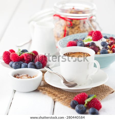 Healthy breakfast - cup of coffee, muesli and fresh berries on white wooden background, selective focus, health and diet concept - stock photo