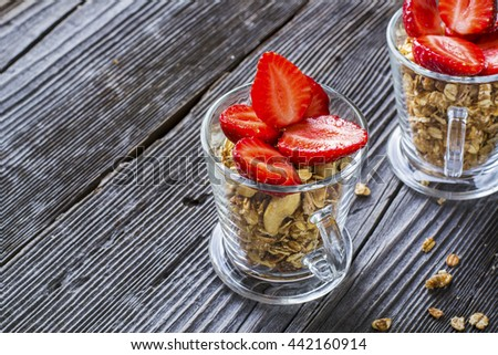 Healthy breakfast dessert. Home crunchy granola with nuts and fresh strawberries in transparent portioned glasses on dark wooden background. selective focus - stock photo