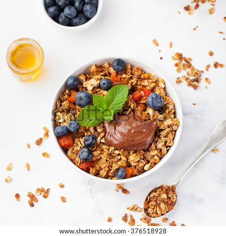 Healthy breakfast Fresh granola, muesli in bowl with milk, berries, chocolate hazelnut spread on a white stone background Top view - stock photo