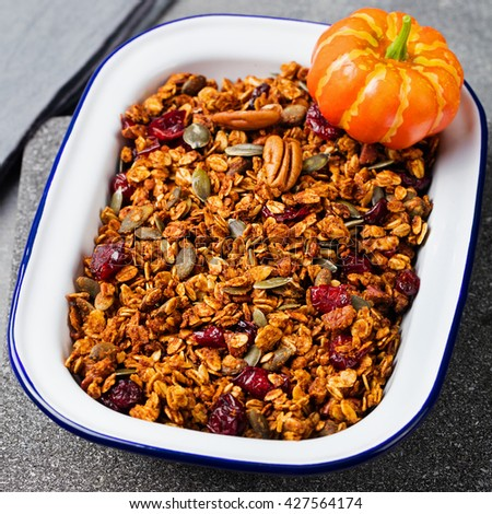 Healthy breakfast. Fresh granola, muesli with pumpkin,pecan nuts,cranberries and maple syrup in white bowl. - stock photo