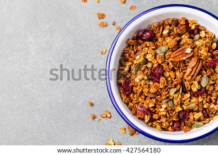 Healthy breakfast. Fresh granola, muesli with pumpkin,pecan nuts,cranberries and maple syrup in white bow. Copy space. Top view - stock photo