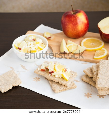 Healthy breakfast. Fresh healthy snack. Fruit salad with crispbread. Apples, lemon, sweet cottage cheese - stock photo