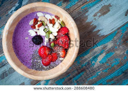 Healthy breakfast fruit smoothie bowl of blueberry and strawberry blended with kefir yogurt and topped with fresh strawberry, chia seeds, goji berries, cashews and pumpkin seeds.