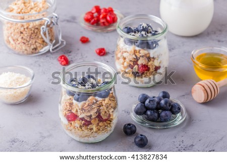 Healthy breakfast - glass jars of oat flakes with fresh fruit, yogurt and honey, selective focus. - stock photo