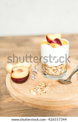 healthy breakfast: granola, cereal, yogurt with peach and plum - stock photo