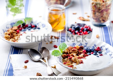 Healthy breakfast. Granola with pumpkin seeds and goji berries, honey, yogurt and fresh berries in a glass on blue and white background. - stock photo
