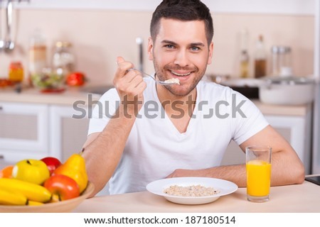 Healthy breakfast. Handsome young man having a healthy breakfast while sitting in the kitchen - stock photo
