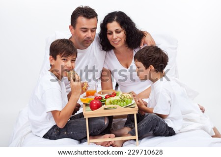 Healthy breakfast in bed - family eating fruits and fresh bakery products - stock photo