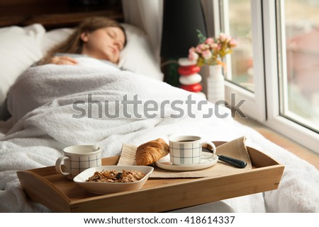 Healthy breakfast in bed with coffee. Sleeping woman in bed.