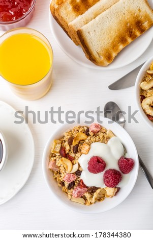 Healthy Breakfast Meal - Bowl of Fruit, Oat and Nut Granola  with Yoghurt and Raspberries - stock photo