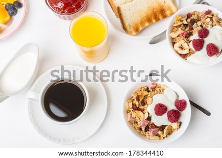 Healthy Breakfast Meal - Bowl of Fruit, Oat and Nut Granola  with Yogurt and Raspberries - stock photo
