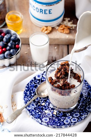 Healthy breakfast. Molasses glazed granola with pecans,walnuts, milk, yogurt and fresh berries in a glass on blue and white background. - stock photo