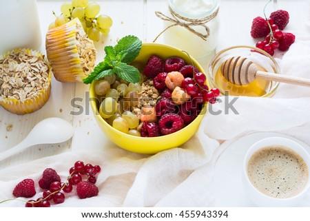 Healthy breakfast: muesli, honey, yogurt, muffins, coffee and fresh berries on white wooden background - stock photo