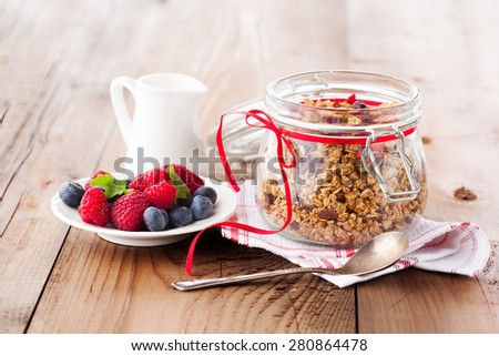 Healthy breakfast -  muesli, milk and fresh berries on rustic wooden background, selective focus, health and diet concept - stock photo