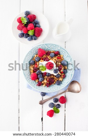 Healthy breakfast - muesli, milk and fresh berries on white wooden background, top view, health and diet concept - stock photo