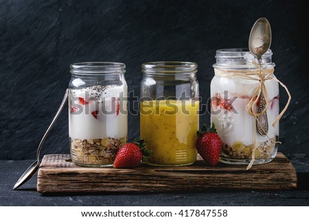 Healthy breakfast muesli, strawberries and yogurt with mango smoothie in glass mason jars. Served on wooden chopping board with fresh strawberry over black background. - stock photo