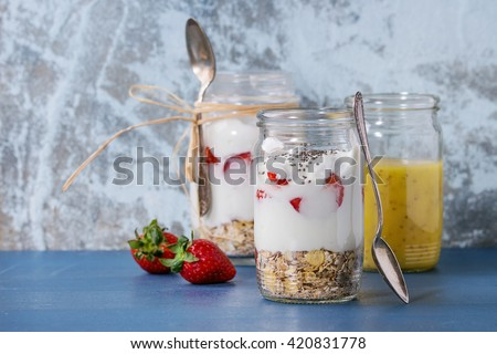 Healthy breakfast muesli, strawberries and yogurt with mango smoothie in glass mason jars. Served on blue wooden table with textured wall at background.