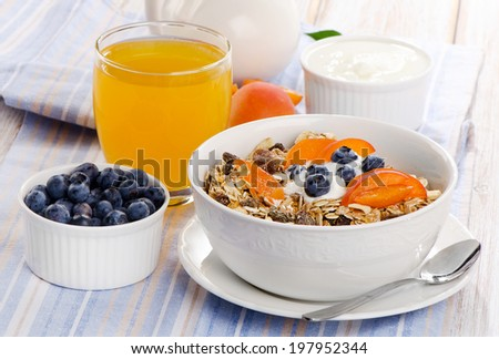 Healthy breakfast - muesli with yogurt and fresh juice . Selective focus - stock photo