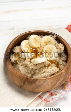 Healthy breakfast: oat bran porridge, banana and agave syrup - stock photo