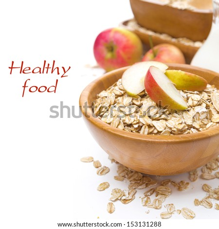 healthy breakfast - oat flakes with apples in a bowl and jug of milk isolated on white - stock photo