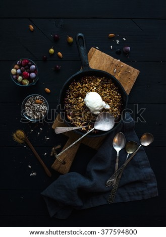 Healthy breakfast. Oat granola crumble with frozen fresh berries, seeds and ice-cream scoop in iron skillet pan on rustic wooden board over dark backdrop, top view