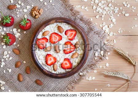 Healthy breakfast oatmeal porridge diet nutririon with strawberry and nuts. Organic vegetarian meal. Vintage wooden table background. Rustic style and natural light. - stock photo