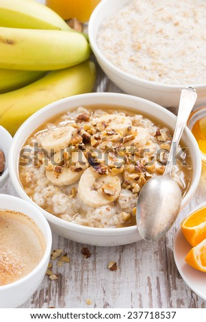 healthy breakfast - oatmeal with banana, honey and walnuts, vertical, top view