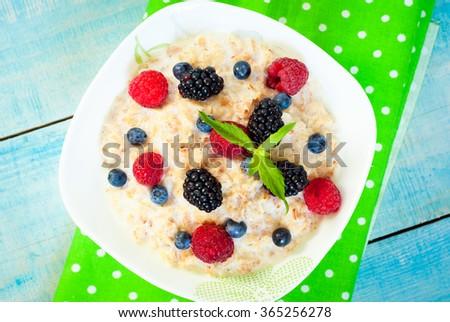 Healthy breakfast - oatmeal with blackberries, blueberries and raspberries.? Top view. - stock photo