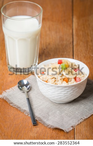 Healthy breakfast. Oatmeal with candied fruits and milk on wooden table