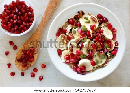 Healthy breakfast oatmeal with pomegranate, bananas, seeds and nuts, overhead scene on white marble