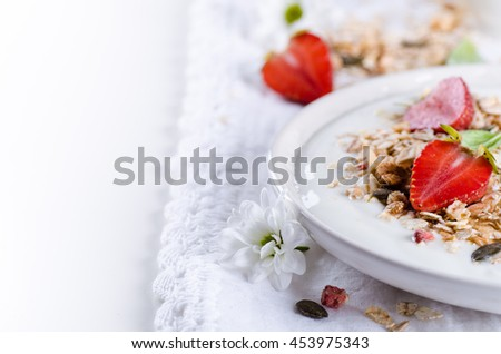 Healthy breakfast of homemade granola with yogurt and berries closeup on white background