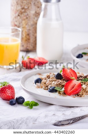 Healthy breakfast of homemade granola with yogurt and berries on rustic background - stock photo