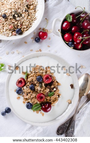 Healthy breakfast of homemade granola with yogurt and berries on white background - stock photo