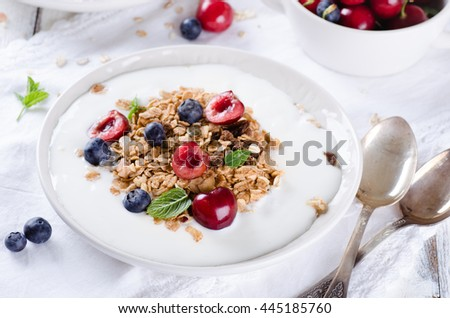 Healthy breakfast of homemade granola with yogurt and berries on white background